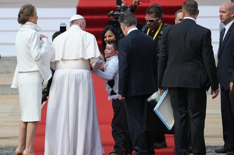 El papa Francisco se detuvo para saludar a niños que se acercaron antes de ingresar a la Casa de Nariño. (Foto Prensa Libre: EFE)