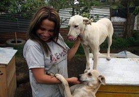 Karla Chacón convive con dos de los perros que atienden en el refugio. (Foto Prensa Libre: Renato Melgar).