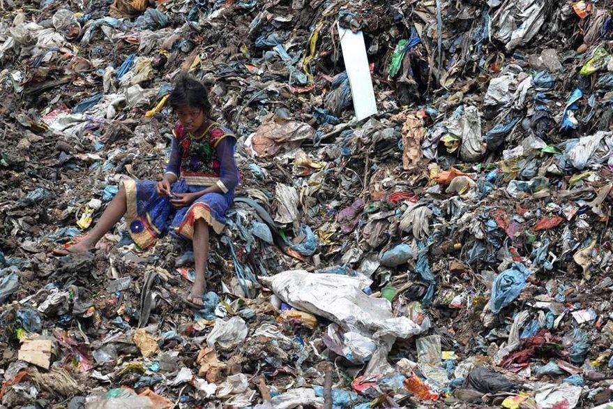 Una niña busca reciclar basura en un enorme basurero de la India. (Foto Prensa Libre: AP).