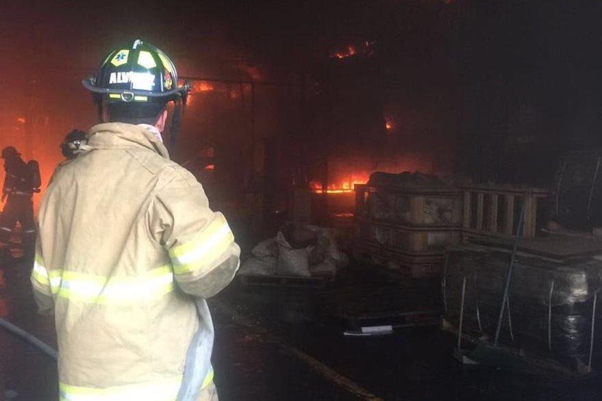 Un bombero voluntario intenta extinguir las llamas en la bodega de calzado en la zona 12. (Foto Prensa Libre: CVB)