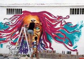 Un niño observa a la artista canadiense María Rosa Szychowska mientras pinta un mural en el barrio El Rastro, Puerto Barrios, Izabal. (Foto Prensa Libre: Dony Stewart)