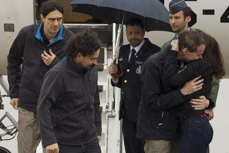 Los periodistas españoles, Antonio Pampliega, (abraza a una familiar), José Manuel López, (izquierda) y Ángel Sastre, en el momento que arriban a la base militar Torreón de Madrid, España. (Foto Prensa Libre: AP).