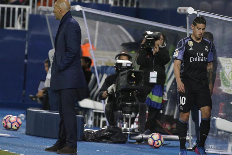 James Rodríguez sale molesto del estadio por el cambio. Observa a su entrenador, Zinedine Zidane. (Foto Prensa Libre: EFE)