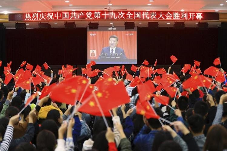 Estudiantes agitan banderas durante el discurso del presidente chino, Xi Jinping. (Foto Prensa Libre: AP)