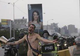 Momento en que manifestantes desnudo pedía frenar el lanzamiento de bombas en Caracas, Venezuela. (Foto Prensa Libre: AP)