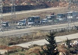 Cuatro autobuses trasladan a personas evacuadas a Ramoussa, en las afueras de Alepo. (Foto Prensa Libre:AFP).