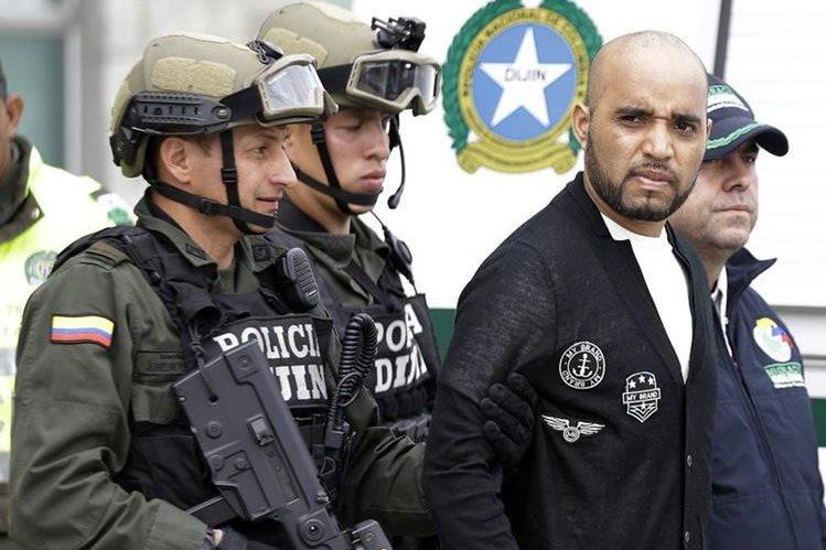 Gerson Gálvez (izquierda), es escoltado por miembros de seguridad colombianos previo a abordar el avión que lo llevó hasta Perú. (Foto Prensa Libre: AP).