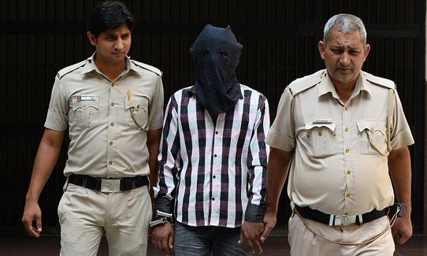 Ravinder Kumar, es escoltado por dos guardias después que fue detenido acusado de violación y asesinato de menores. (Foto: Mail Online News).