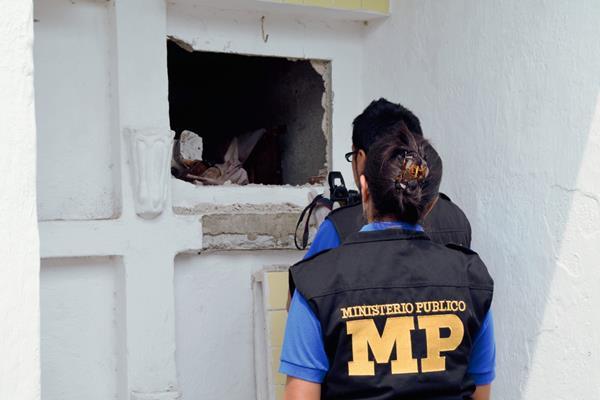 Fiscales del Ministerio Público inspeccionan la tumba profanada en el cementerio general de Retalhuleu. (Foto Prensa Libre: Jorge Tizol)