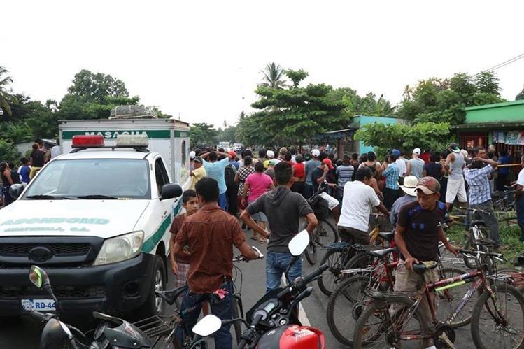 Curiosos permanecen en el lugar donde murió baleada la víctima. (Foto Prensa Libre: Enrique Paredes).