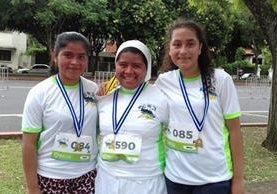 Marta Alicia Caal Alcántara – al centro – junto a dos corredoras. (Foto Prensa Libre: Cortesía)
