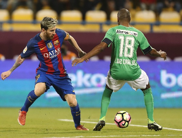 Messi, del Barsa, disputa el balón con Luiz Carlos, del Al-Ahlis. (Foto Prensa Libre: AFP).