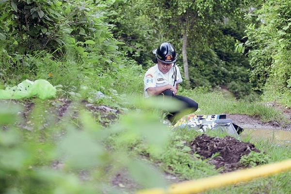 Un paramédico de Bomberos Voluntarios, examina el cadáver desmembrado de una mujer en la zona 25. (Foto Prensa Libre: Erick Ávila)