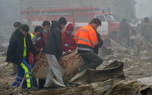 Recatistas trasladan el cuerpo de una de las víctimas del accidente aéreo. (AFP).