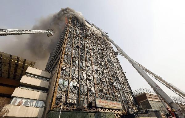 Bomberos trabejan por extingir las llamas del edificio Plasco en Teherán, Irán. (EFE).
