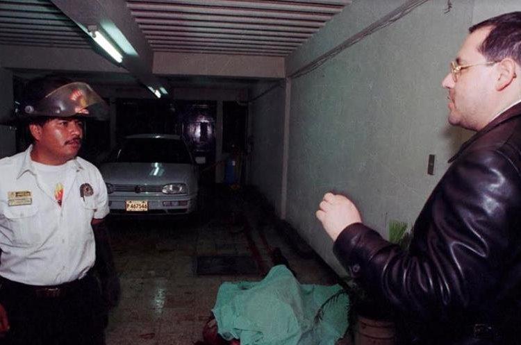 El sacerdote Mario Orantes se dirige a un socorrista mientras el cuerpo del monseñor permanecía en el suelo.