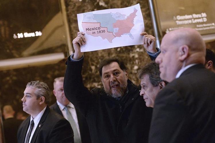 El exdiputado Fernández sostiene un mapa de México y EE. UU., en la Torre Trump de Nueva York, contra los planes migratorios de Trump.(Foto Prensa Libre: EFE).