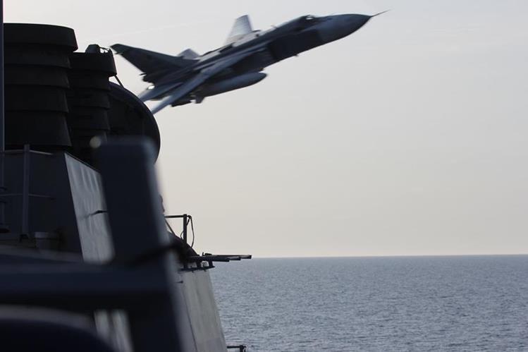 Un avión ruso SU-24 efectúa un pase de corto alcance cerca de un buque estadounidense. (Foto Prensa Libre: AP).