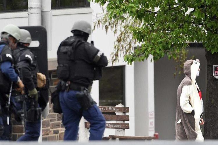El hombre con el extraño disfraz parecido a un panda, sale del canal de TV ante la mirada de la policía. (Foto Prensa Libre: AP).