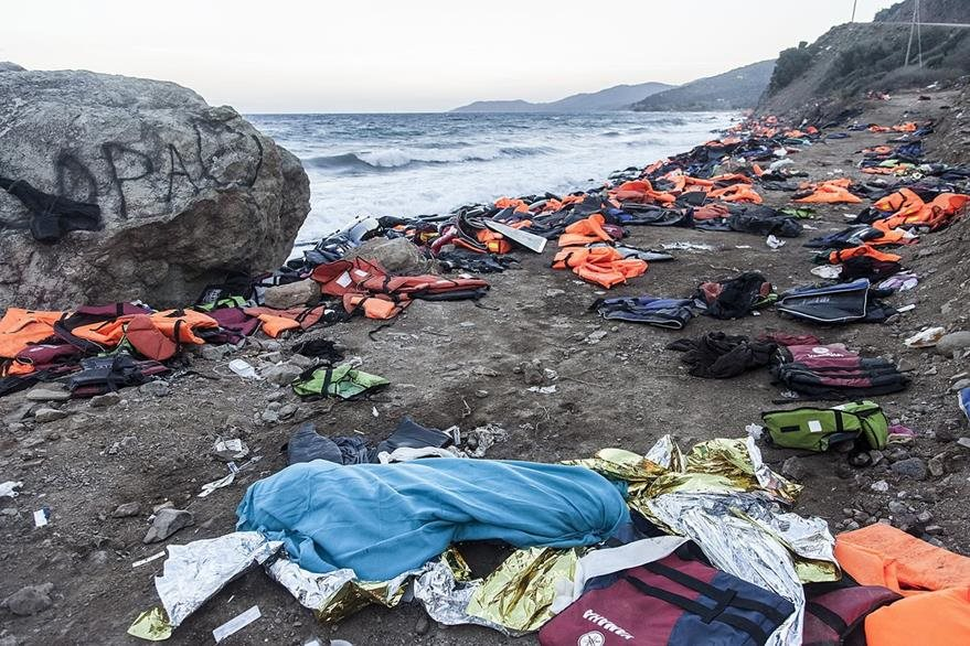 El cadáver de una persona se observa en las costas del mar Egeo junto a decenas de chalecos salvavidas. (Foto Prensa Libre: EFE).