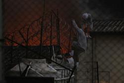 Internos caminan por el techo de uno de los ambientes. Al fondo, un incendio. (Foto Prensa Libre: Paulo Raquec)