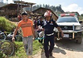Socorristas trasladan a dos personas que resultaron heridas al caer a un pozo. (Foto Prensa Libre: Víctor Chamalé)