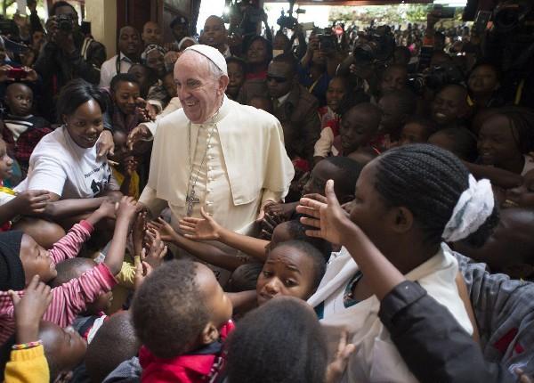 El papa Francisco (centro) saluda a un grupo de niños durante su visita a Nairobi,Kenia. (Foto Prensa Libre:EFE).