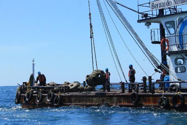 <p>Personal  de la Empresa Portuaria Quetzal traslada estructuras en barcaza.</p>