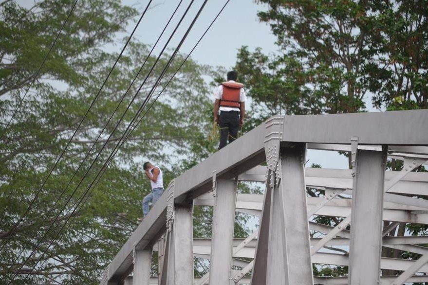 El bombero voluntario Marcos Chávez conversa con Elvin Elías Colop Mendoza, quien amenazaba con suicidarse. (Foto Prensa Libre: Jorge Tizol)