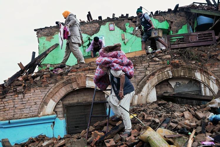 Sobrevivientes del terremoto rescatan pertenencias de una casa que fue dañada en Katmandú, Nepal, (Foto Prensa Libre AP)