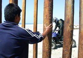 Un inmigrante mira desde México a un oficial de la patrulla fronteriza de EE. UU. (Foto Prensa Libre: Hemeroteca PL)