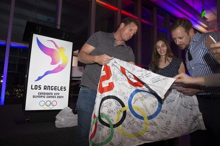 Atletas firman una bandera olímpica durante la presentación del logotipo de la candidatura de los JJOO Los Ángeles 2024. (Foto Prensa Libre: EFE)