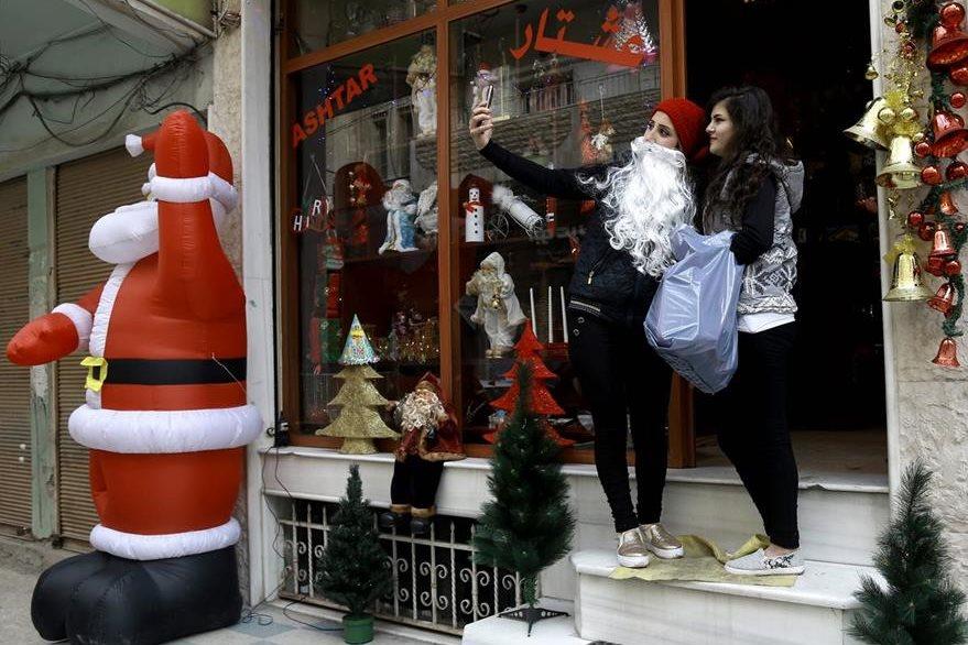 Dos jóvenes sirias se toman fotografías frente a un negocio en el barrio cristiano de Qamishli. (Foto Prensa Libre: AFP).