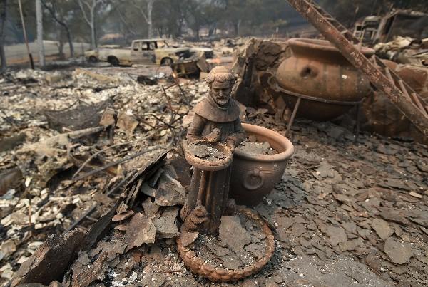 Una escultura quedó entr los escombros de una casa destruida por el fuego.