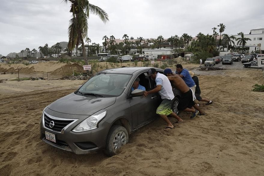 Turistas movilizan su vehículo en Cabo San Lucas, Mexico, luego del paso del huracán Newton. (Foto Prensa Libre: AP).