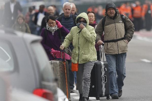 Varios pasajeros evacúan el aeropuerto de Zaventem depués de los atentados.