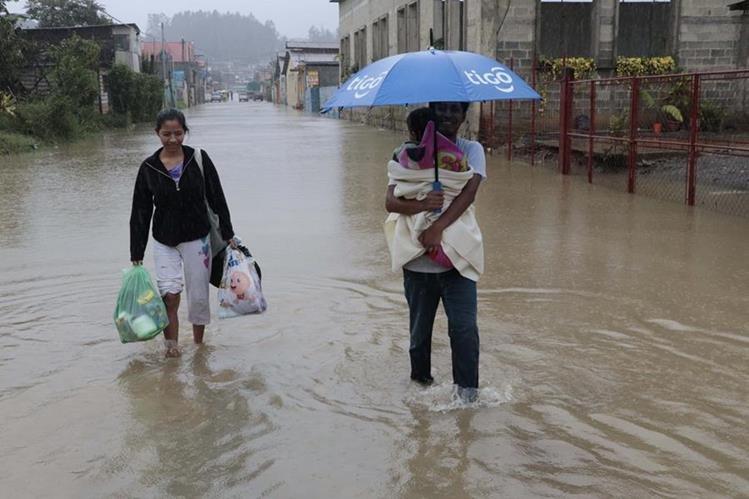 Carlos García junto a su familia caminan por una de las calles de Residenciales Imperial, zona 7, de Cobán, que fue inundada por la crecida del río Cahabón. (Foto Prensa Libre: Eduardo Sam Chun)
