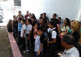 Padres de familia junto a sus hijos permanecen frente al Centro Alida España, luego de una reunión en la que se informó respecto a la suspensión de terapias. (Foto Prensa Libre: Oscar García).