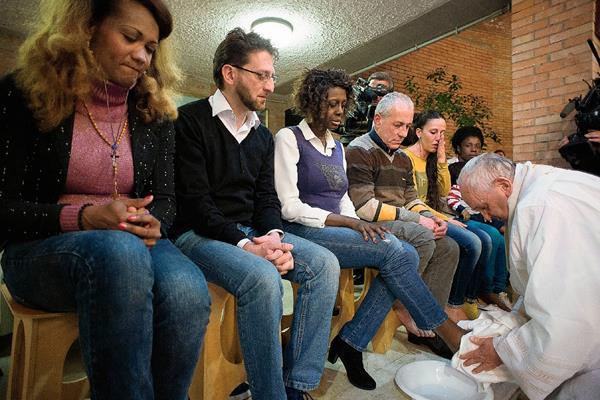El papa Francisco lava los pies de una reclusa durante la conmemoración de Jueves Santo. (Foto Prensa Libre: AFP).