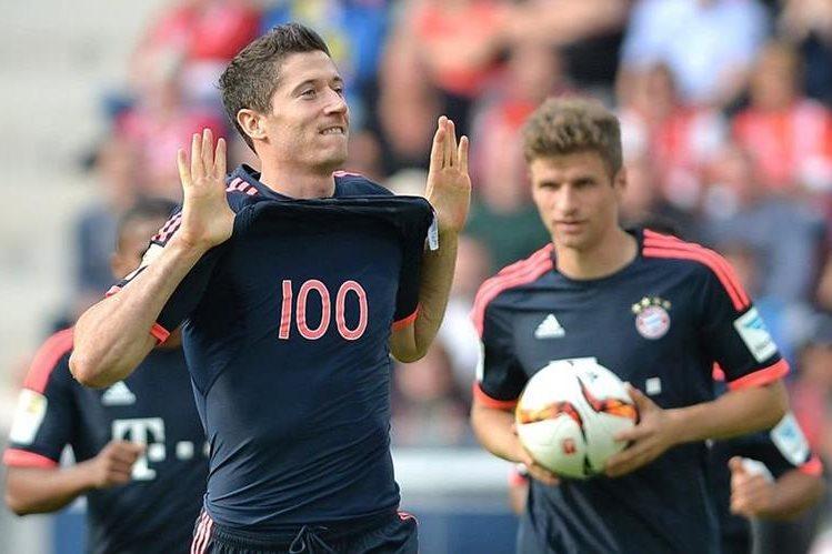 Lewandowski muestra la camisola con el número 100, en honor a su centena de goles en la Bundesliga. (Foto Prensa Libre: EFE)