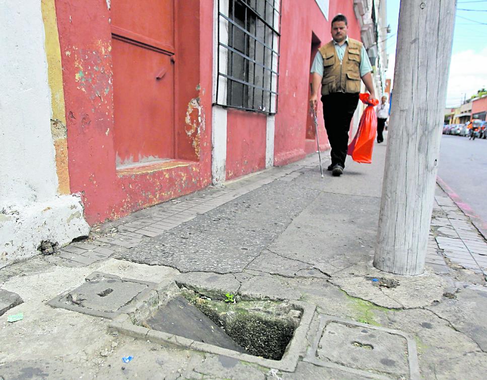 Edwin Sulín, quien tiene dificultad visual, camina por banqueta en mal estado en la 10 calle, entre 11 y 12 avenidas de la zona 1. (Foto Prensa Libre: Esbin García)