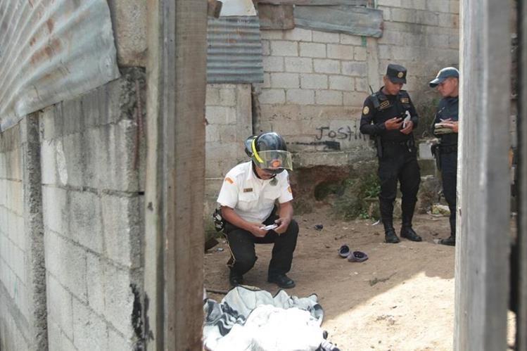 Un bombero voluntarios cubre el cadáver de Alonzo Suruy, luego de confirmar la muerte por lesiones de bala. (Foto Prensa Libre: Erick Avila)