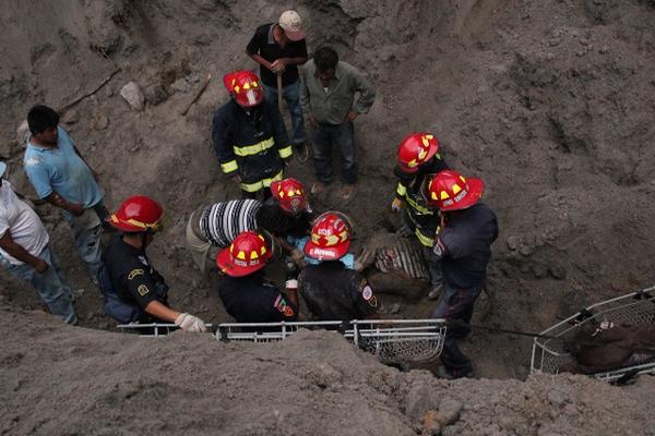 <p>Socorristas trabajan en el rescate de uno de los cadáveres de las personas soterradas en una arenera en El Recreo, San Marcos. (Foto Prensa Libre: Aroldo Marroquín)<br></p>