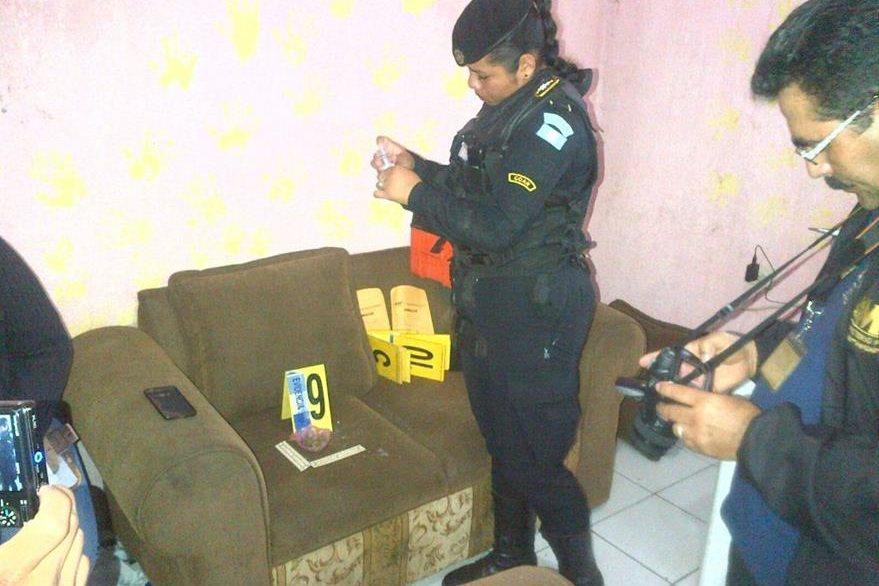 Investigadores  inspeccionan parte de los objetos decomisados a los tres detenidos. (Foto Prensa Libre: Manuel Romero).