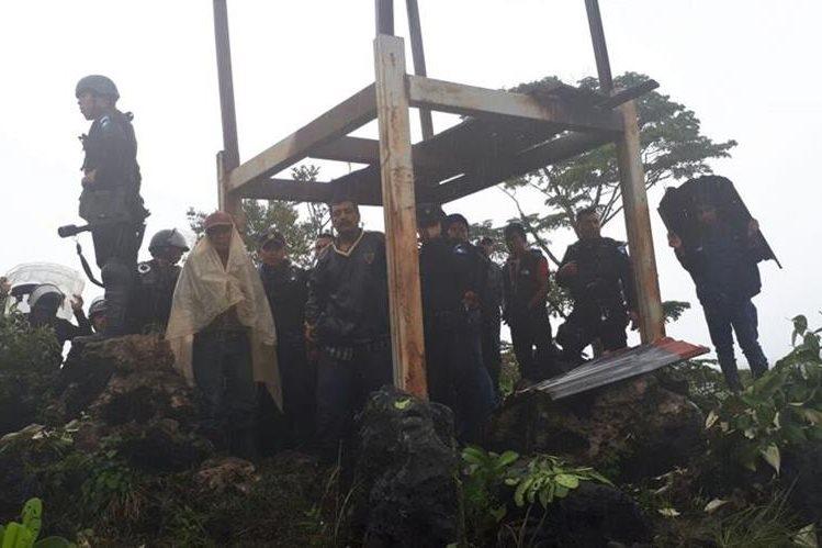 Agentes de la PNC resguarda a un grupo de pobladores que fueron amenazados por los manifestantes. (Foto Prensa Libre: Cortesía PNC)