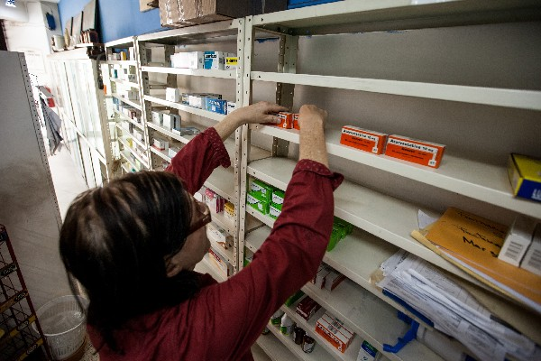Una encargada de una farmacia arregla medicamentos en un estante. (EFE).