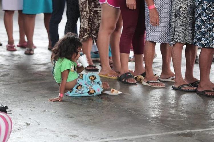 Una niña espera a su mamá mientras hacen fila para recibir ayuda.