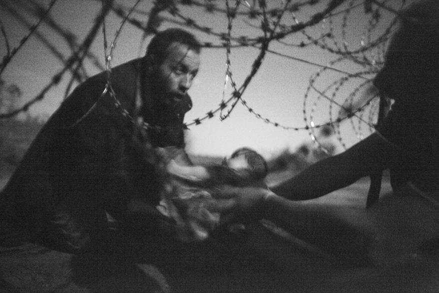 La fotografía ganadora del World Press Photo del 2015 fue esta: la imagen de un migrante pasado entre los alambres alambrados a su bebé en la frontera entre Serbia y Hungría, sintetizaba el drama de los inmigrantes. (Foto Prensa Libre: Hemeroteca PL).