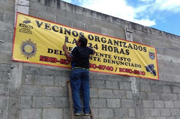 Un vecino del barrio Chichochoc, zona 5, coloca una de las mantas donde se lee que están organizados. (Foto Prensa Libre: Eduardo Sam Chun)