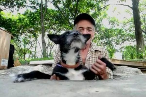 "<p>Restrepo ayuda a su mascota ""Negrita"" a salir de la alcantarilla. (Foto Prensa Libre: AFP)</p>"